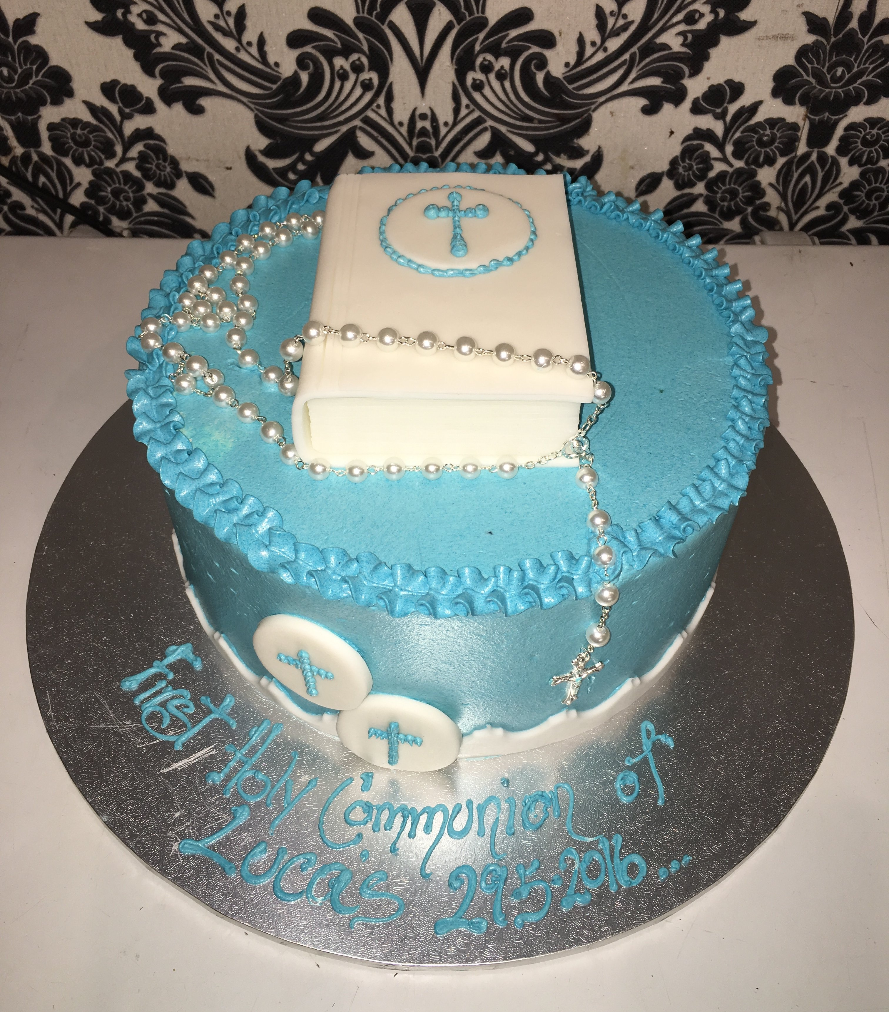 white christening cake with blue cross on top letter boxes below
