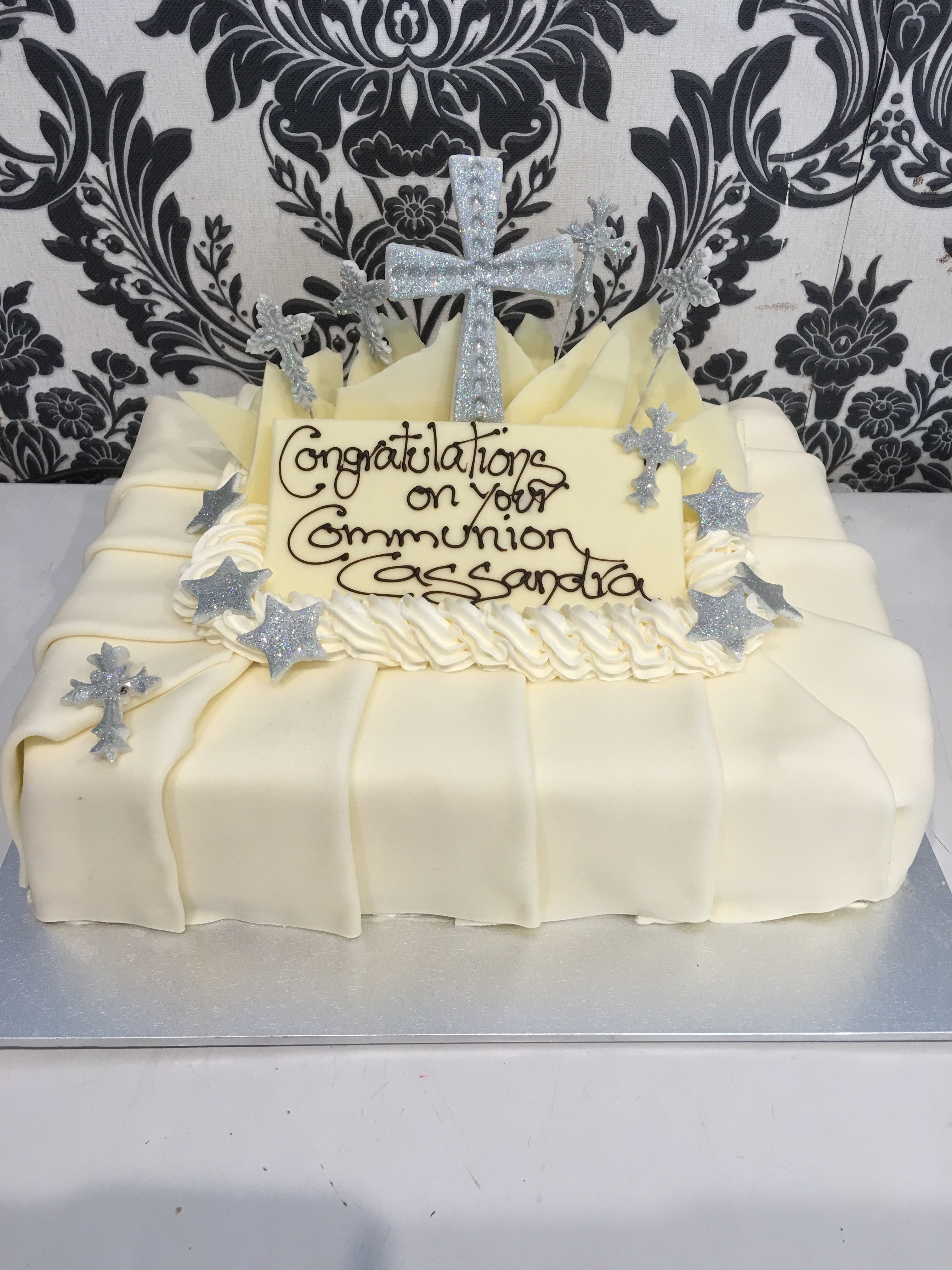 white holy communion cake with silver cross on top