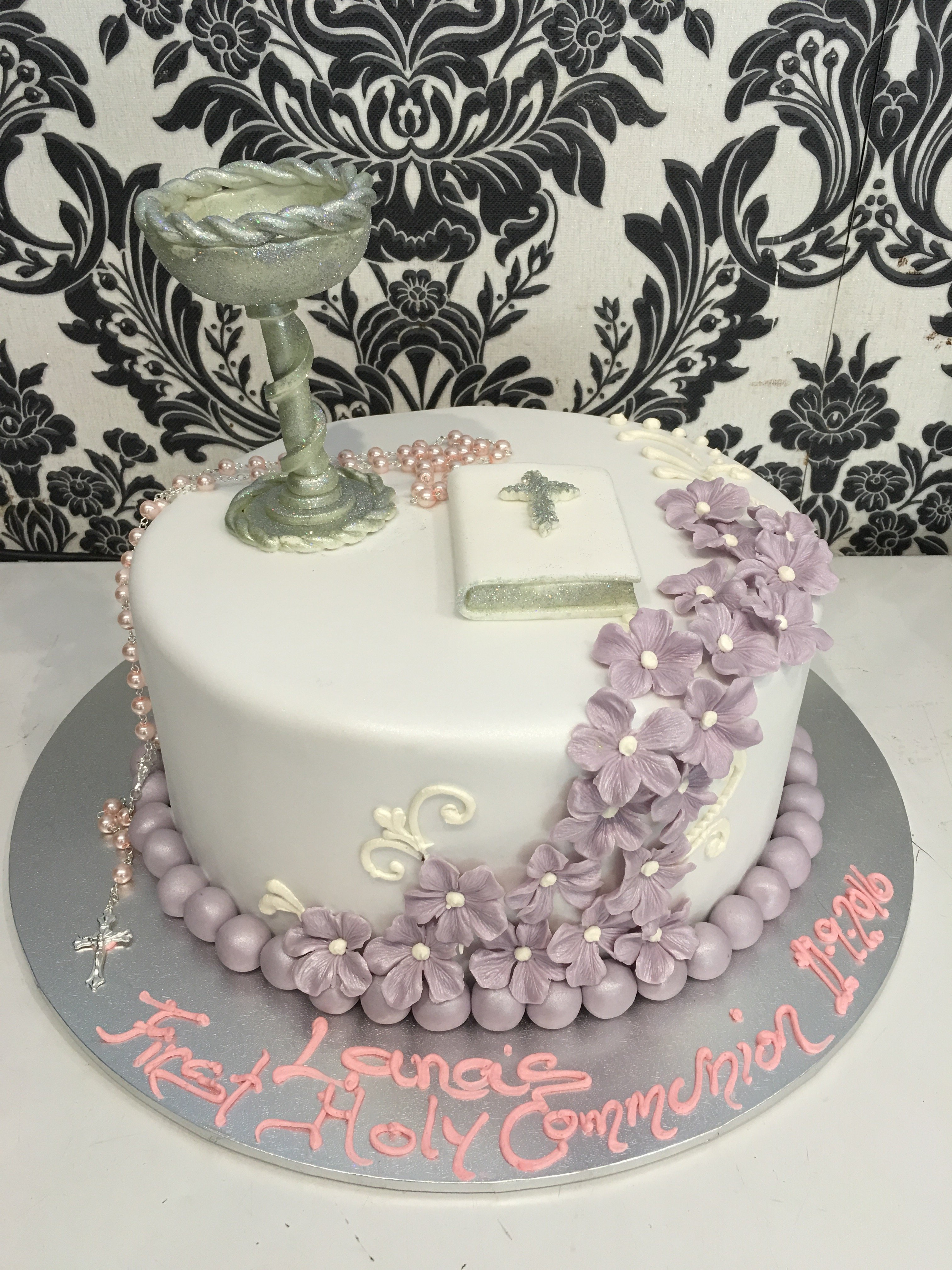white holy communion cake with purple flower details