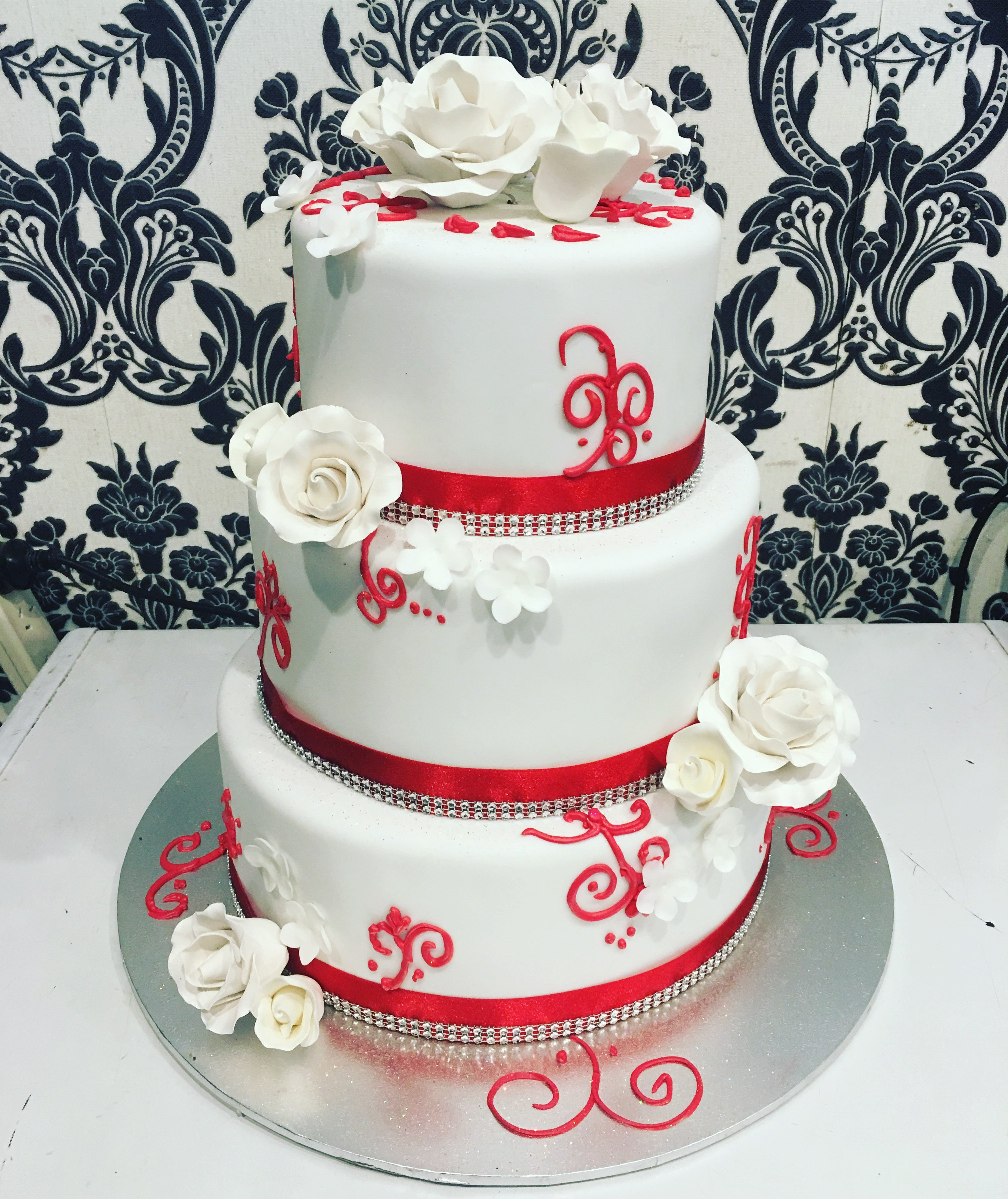 white triple layer cake with red accents and white flowers