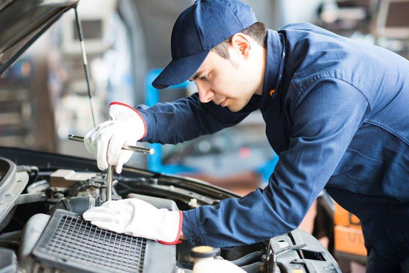 un meccanico con una tuta e un cappello blu mentre sta riparando una vettura con il cofano aperto