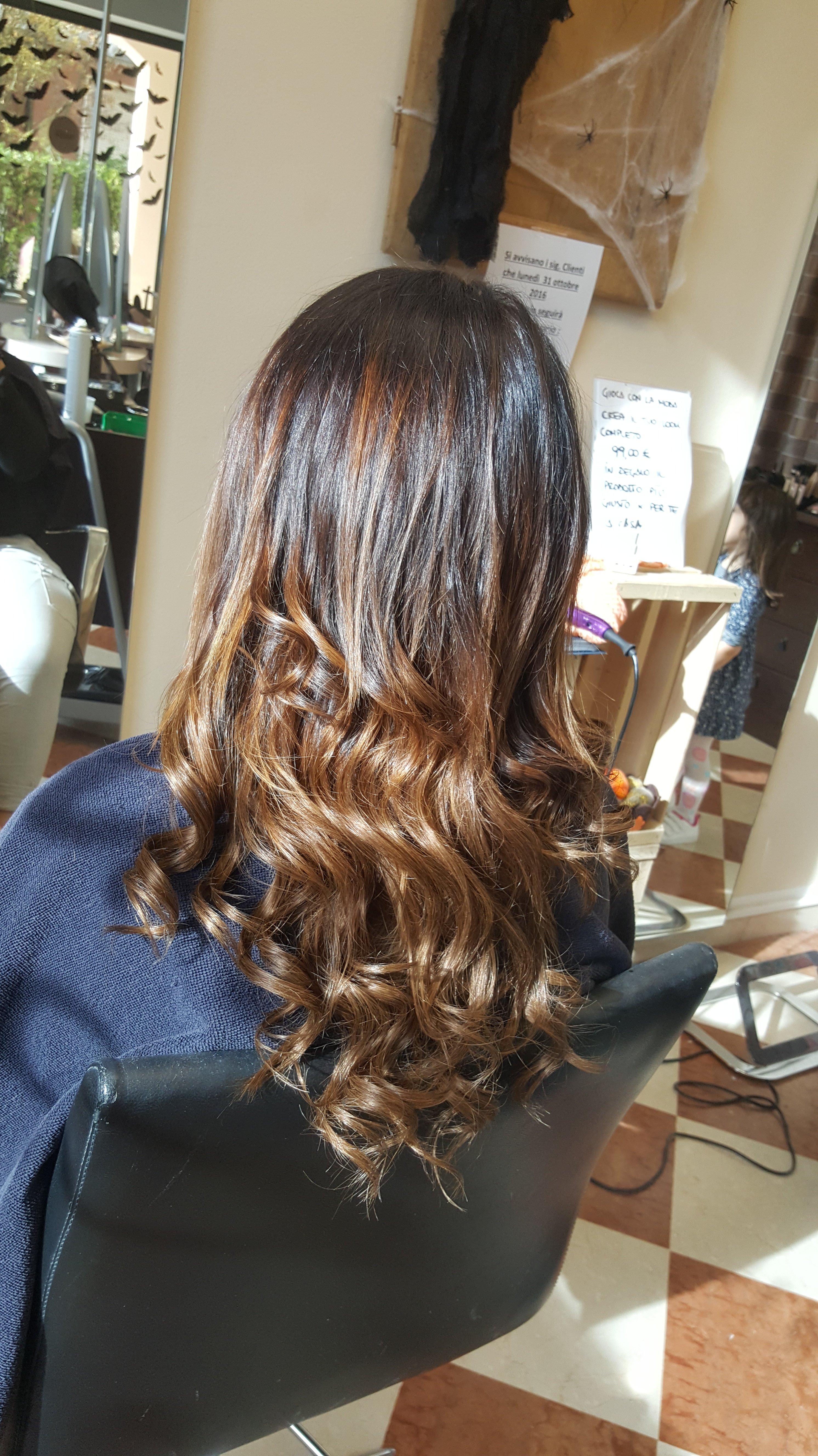 donna dai capelli castani con delle extention mosse