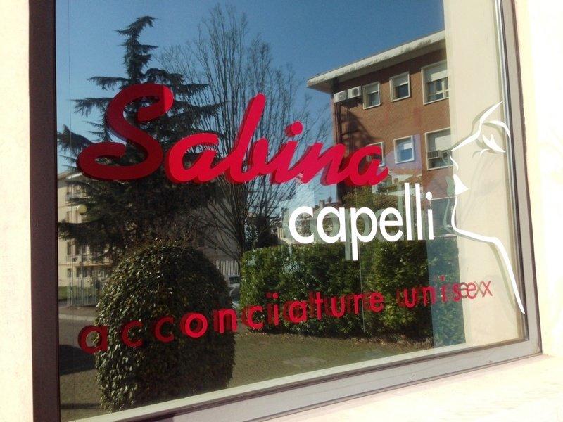 una vetrata con scritto Sabina capelli acconciature unisex e il profilo di una donna disegnato