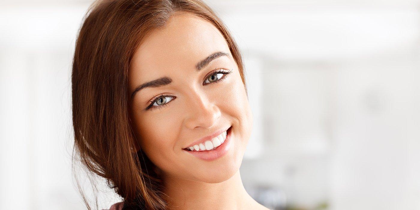 una ragazza con capelli castani e occhi chiari mentre sorride
