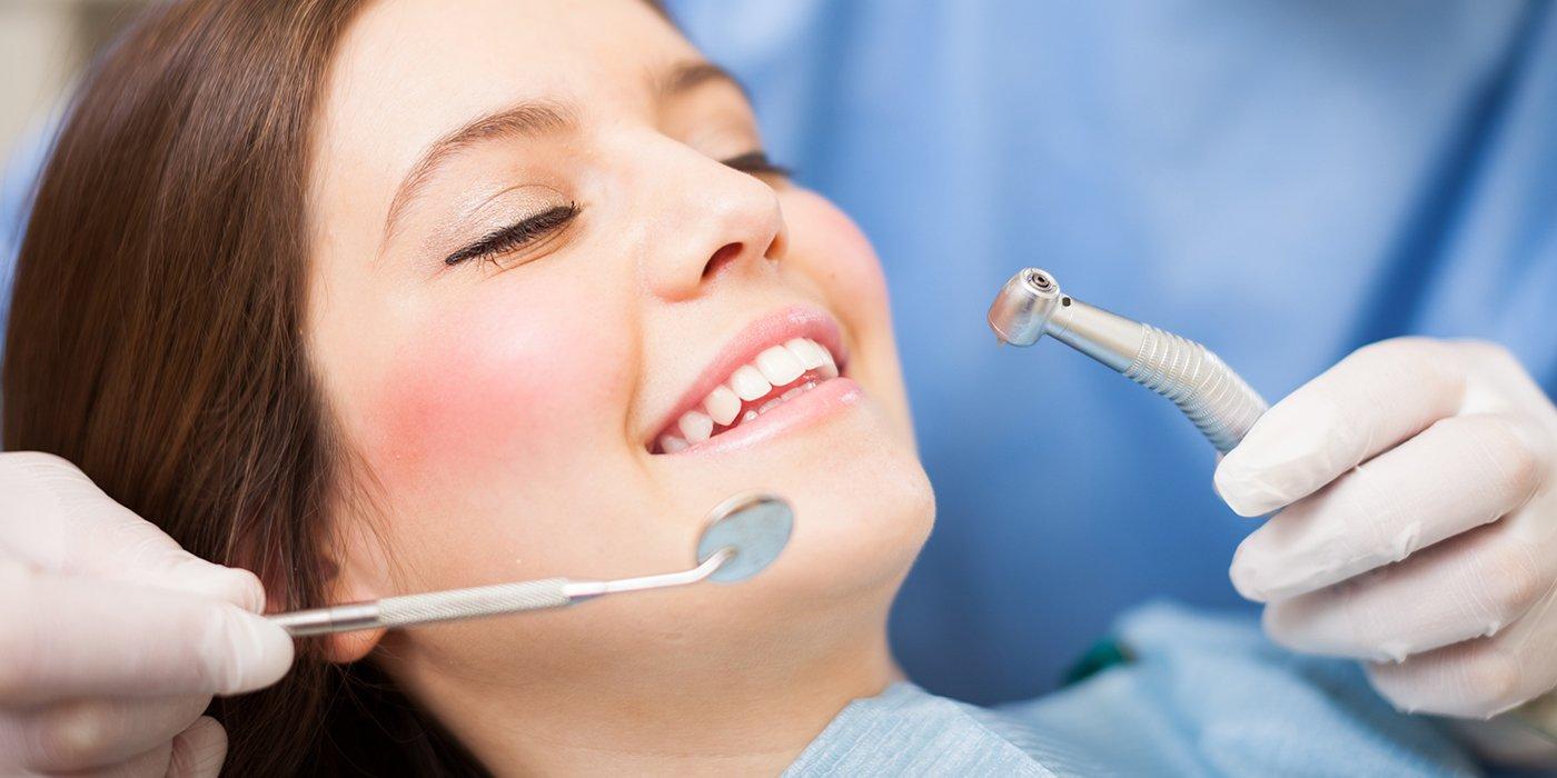 una ragazza sdraiata con gli occhi chiusi mentre sorride e due mani di un dentista con in mano uno specchietto e una turbina