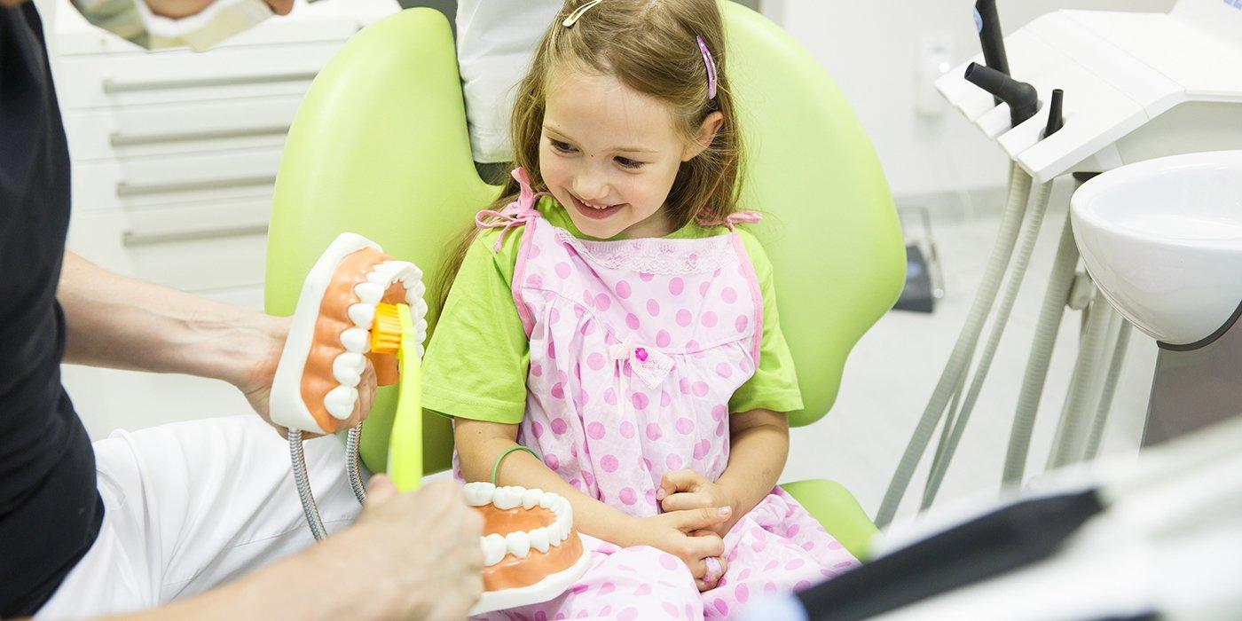 una bambina con una maglietta verde e un grembiule rosa a pois mentre ride guardando una protesi gigante in plastica di una dentatura con uno spazzolino giallo