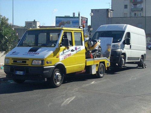 un carrattrezzi giallo con un auto a rimorchio