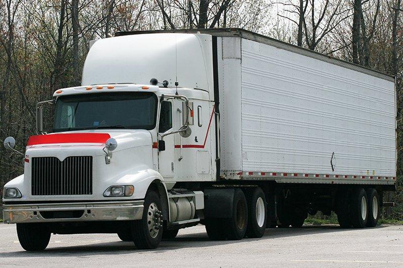 un camion bianco con un lungo rimorchio