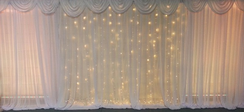 White Fairy curtain shown with white chiffon wall drapes on either side and wall wash lights 9 meters wide.Hire price from $500 incl installation, pick up & gst