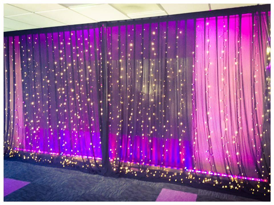 Purple wall wash lights under white chiffon drapes