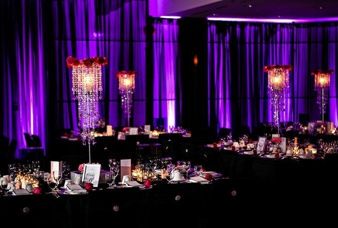 Purple wall wash lighting on black chiffon wall draping.