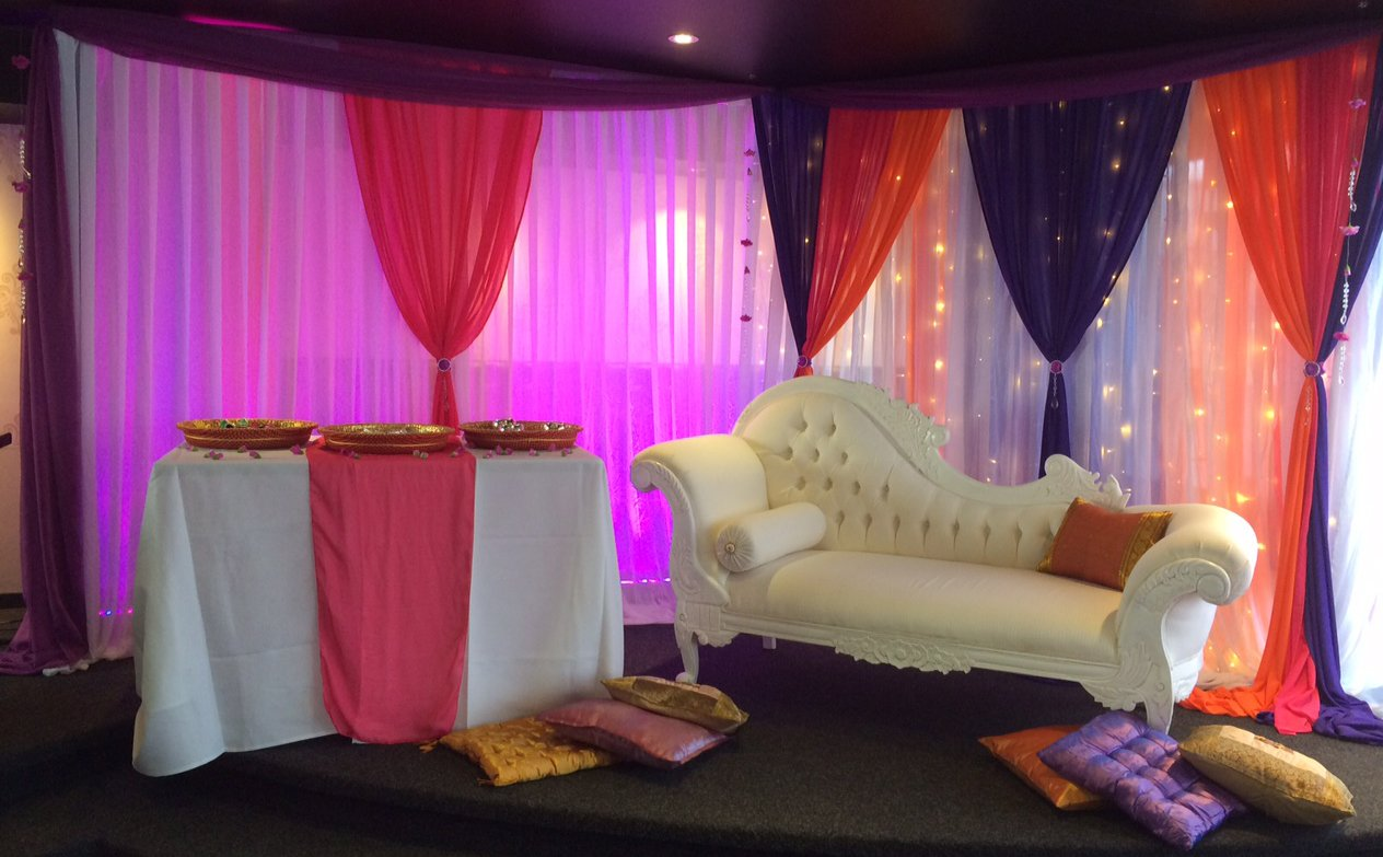 Bespoke wall draping with lighting and flowers suspended from ceiling for a clients Mehndi night (Henna night) at Bollywood Resturant