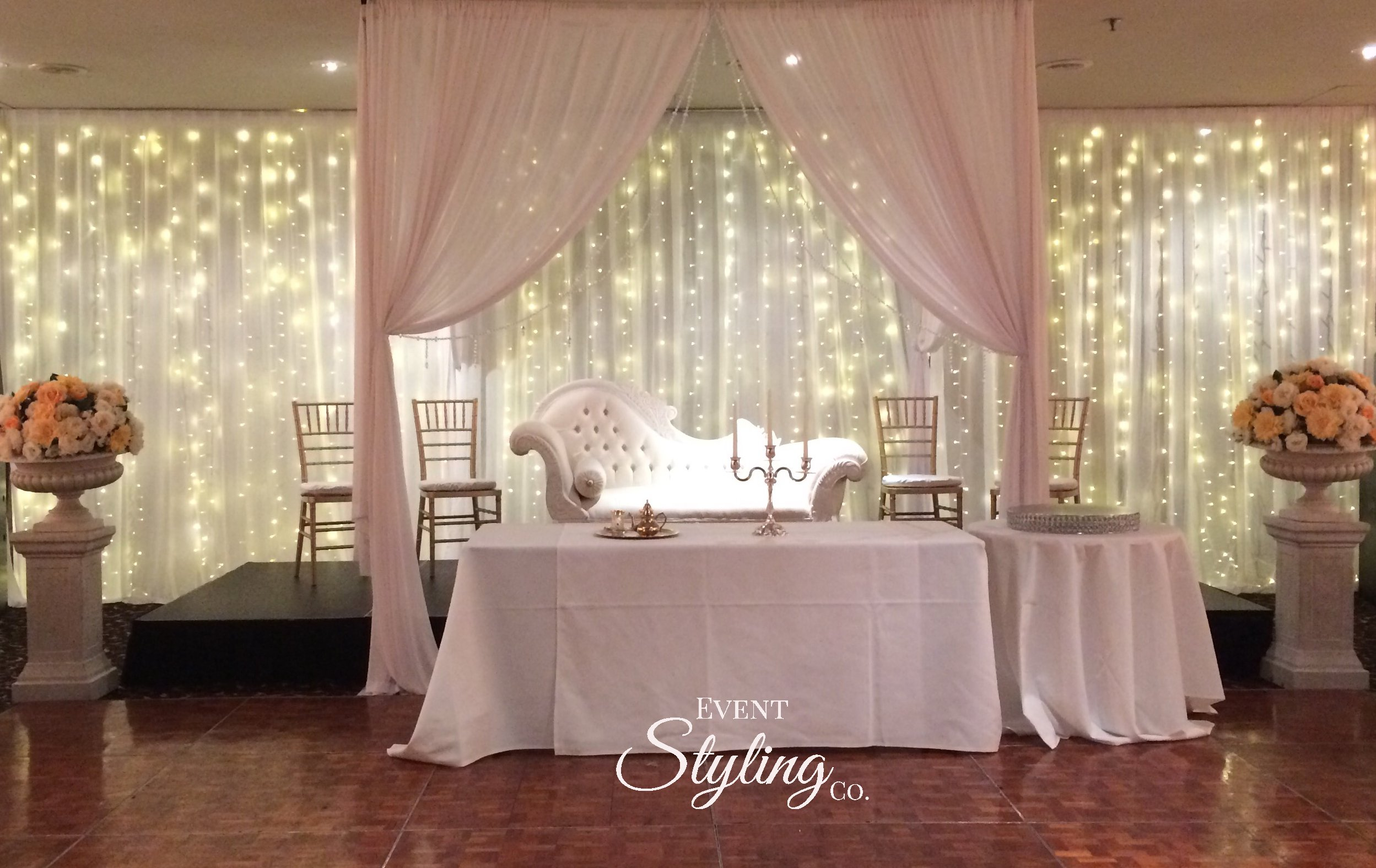 Fairy light curtain wall draping and draped fabric archway at wedding reception at Ellerslie Event centre Auckland