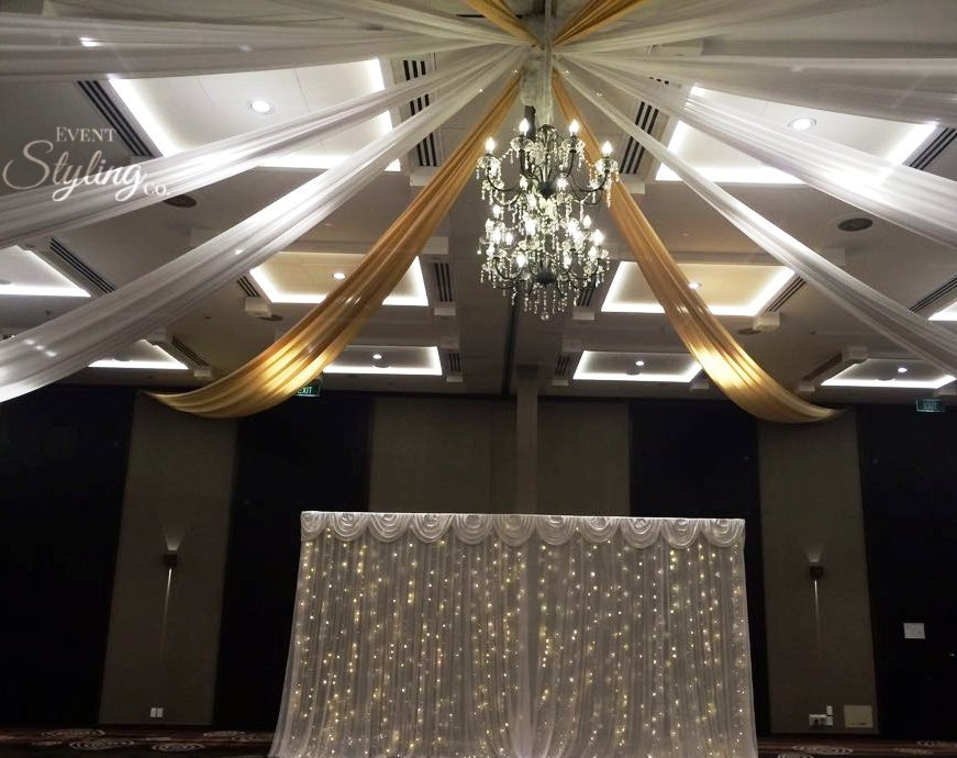 Gold and white ceiling draping with vintage chandeliers and white fairy curtain backdrop at Crowne plaza hotel Auckland