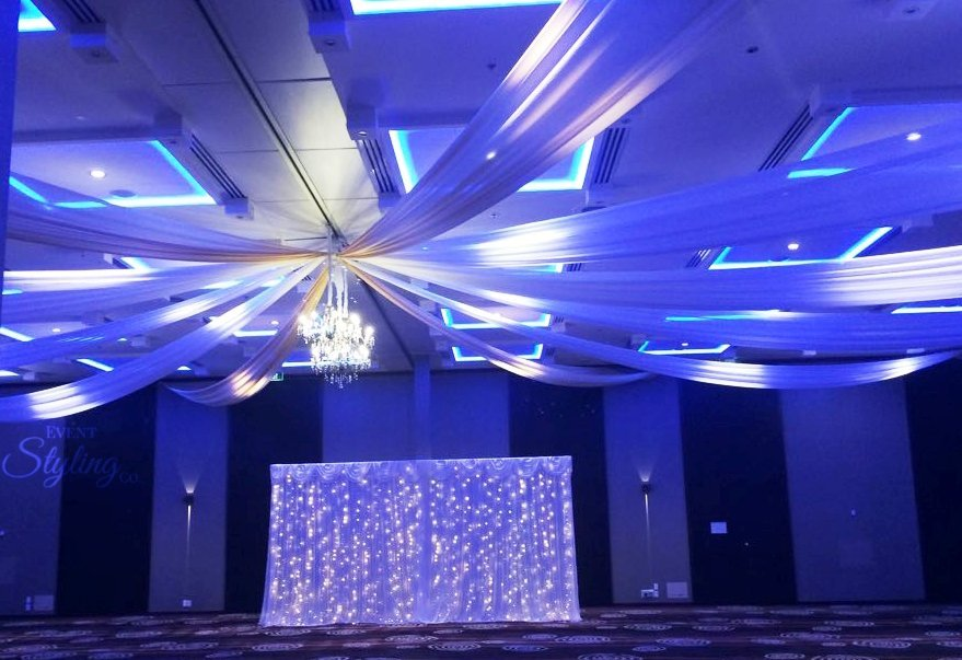 Ceiling draping, lighting and chandelier with white fairy curtain backdrop at Crown Plaza Hotel Auckland.