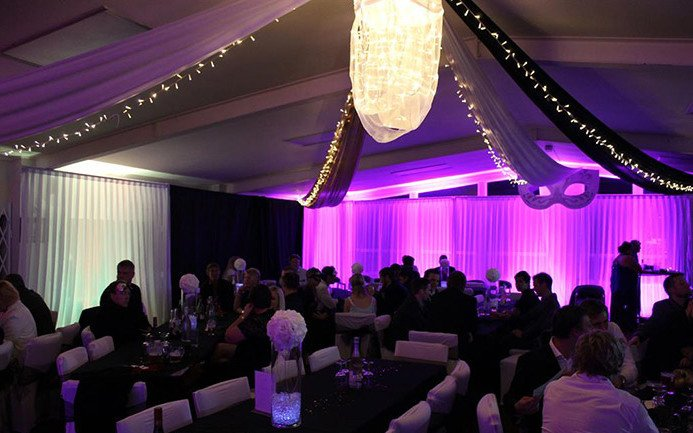 Purple and white lighting on walls with ceiling draping shown in gold, white and black with custom design light at Auckland venue.