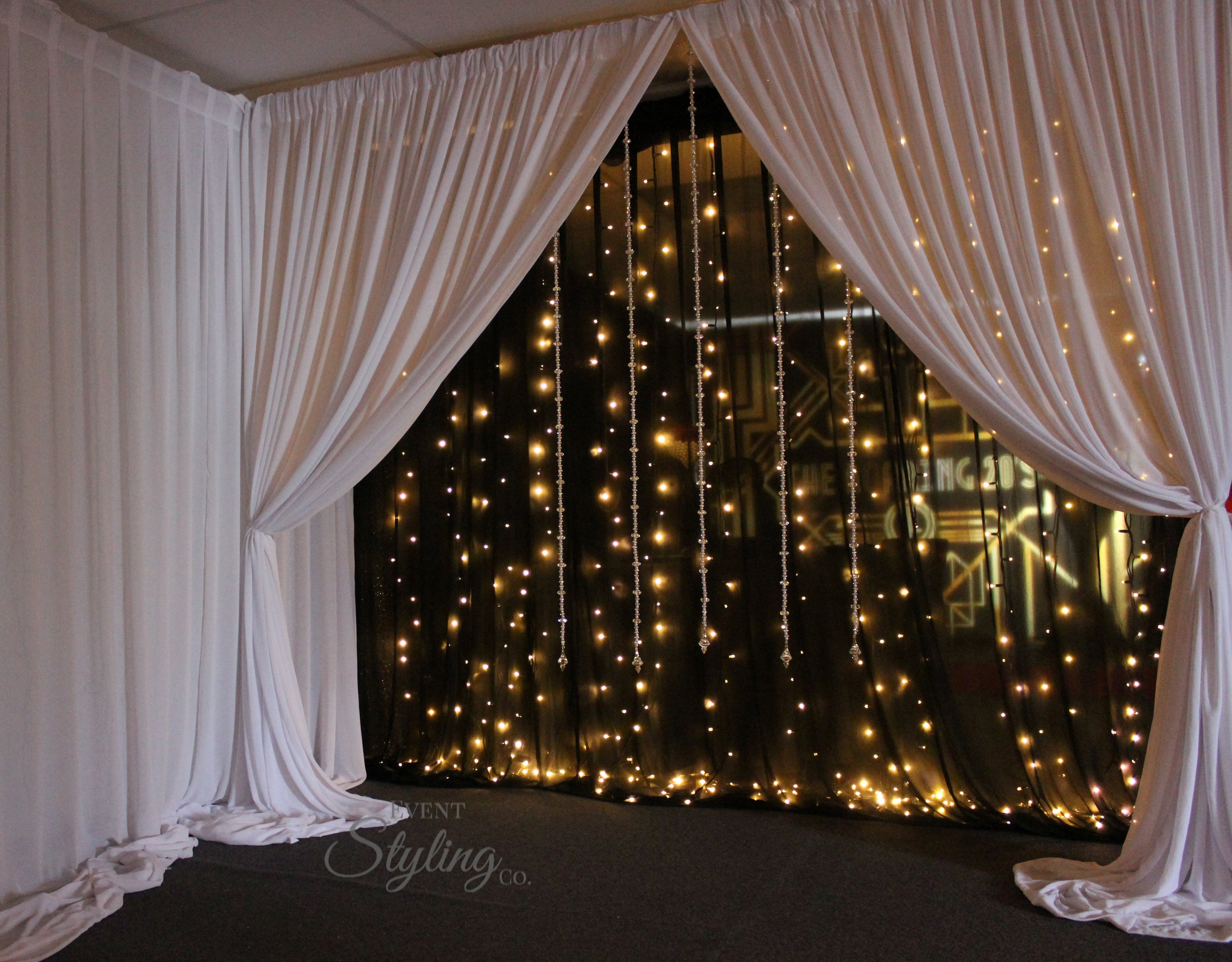 Bespoke black fairy light backdrop with white drapes and crystal starnds in front. Hire price from $450 including Auckland installation