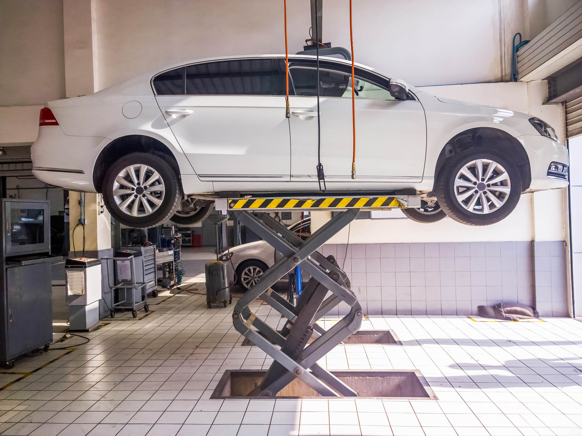 white car being lifted in a shop