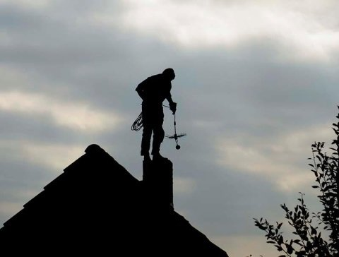 un uomo su un tetto in piedi su una canna fumaria