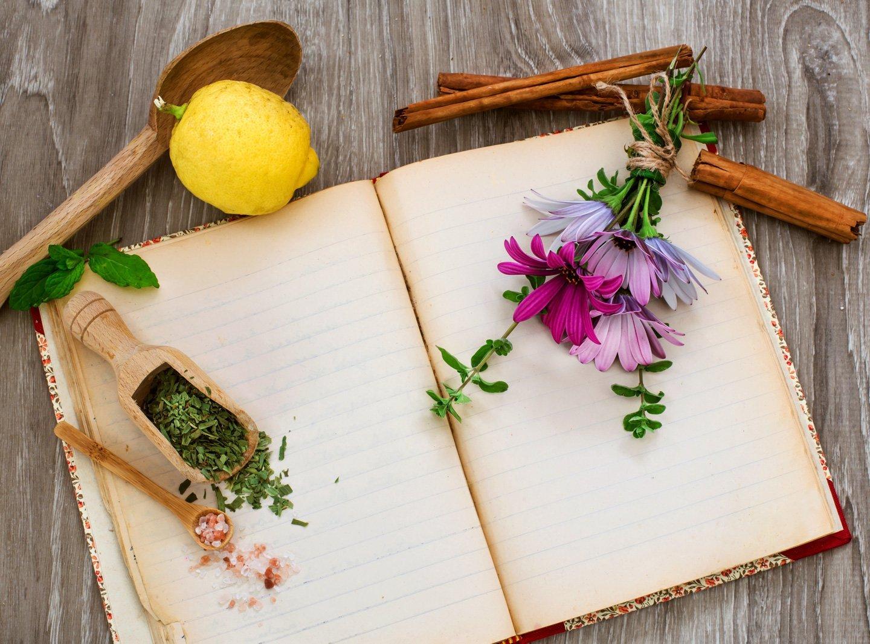 concetto di naturopatia con erbe mediche e fiori su sfondo legno