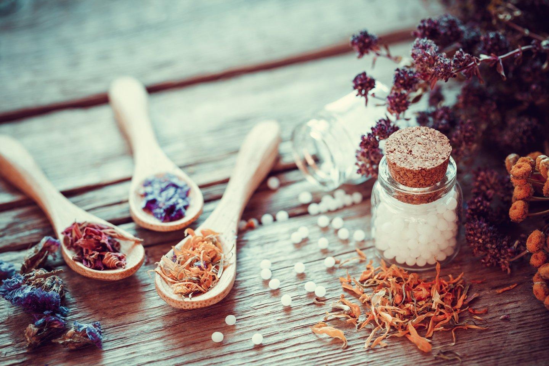 bottiglia di globuli omeopatia, cucchiai di legno e erbe secche