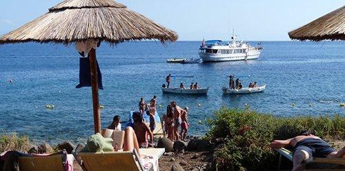 persone in spiaggia con barca all`orizzonte