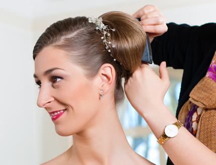 A bride having her hair pulled into a bun