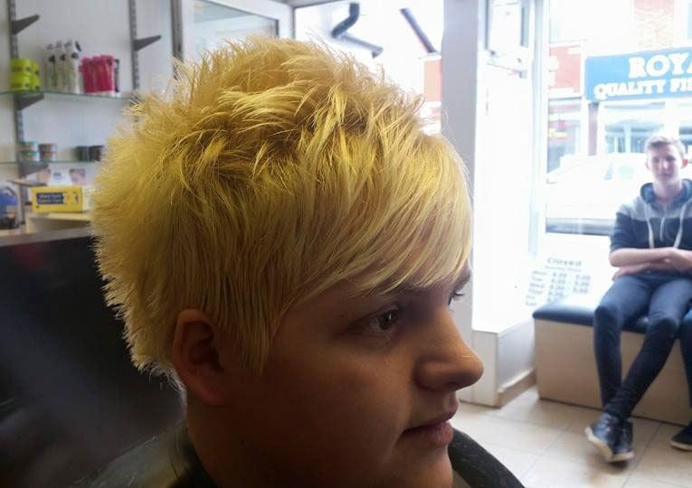 A woman with bleach blonde hair in a short pixie do
