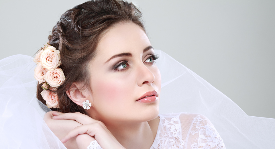 A bride with dark hair, in an up do with peach coloured flowers in her hair