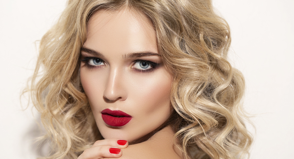 A model with bright red lipstick and nails with wavy blonde hair