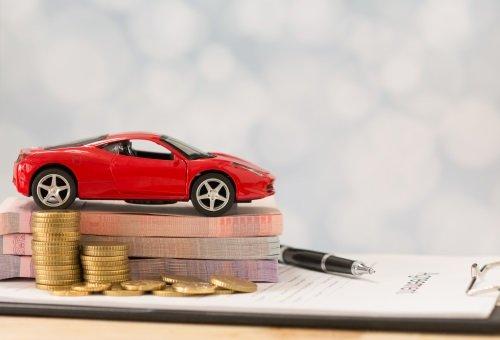 Una macchinina rossa sopra a delle banconote e delle monete