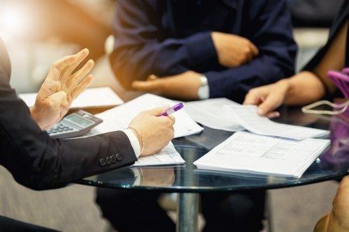 Due mani con una penna e delle persone sedute a un tavolo