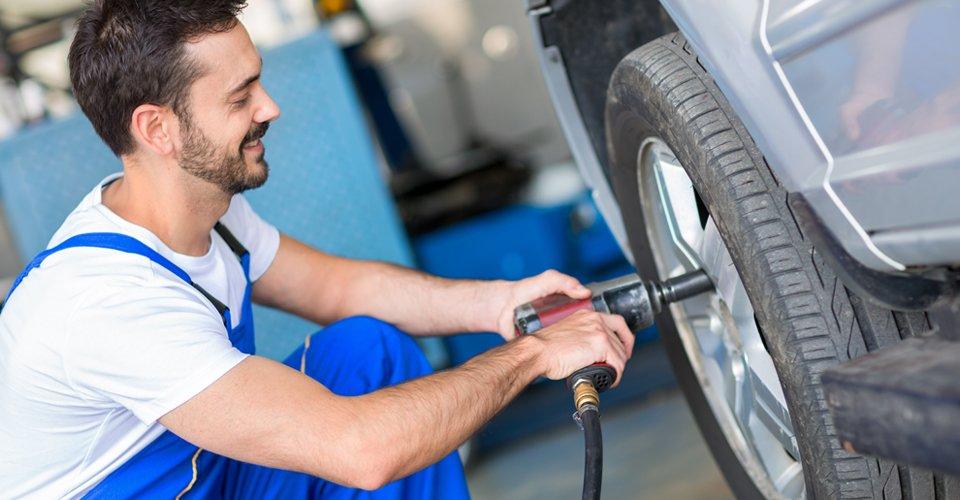 Meccanico cambiando la ruota dell'auto con la chiave impatto