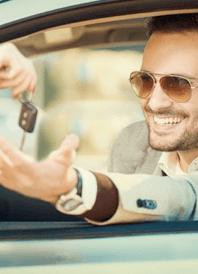 uomo sorride prendendo le chiavi della macchina