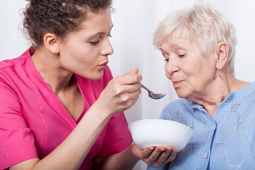 persona dello staff aiuta una donna anziana a mangiare