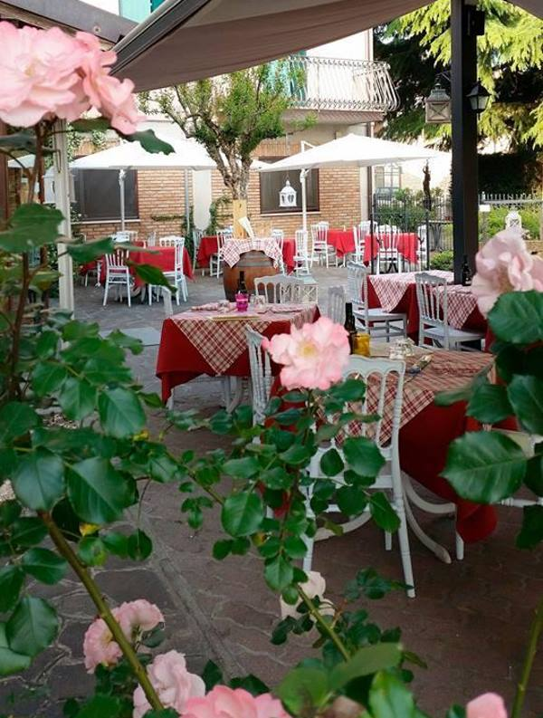 Esterno con tavoli apparecchiati e mazzi di fiori