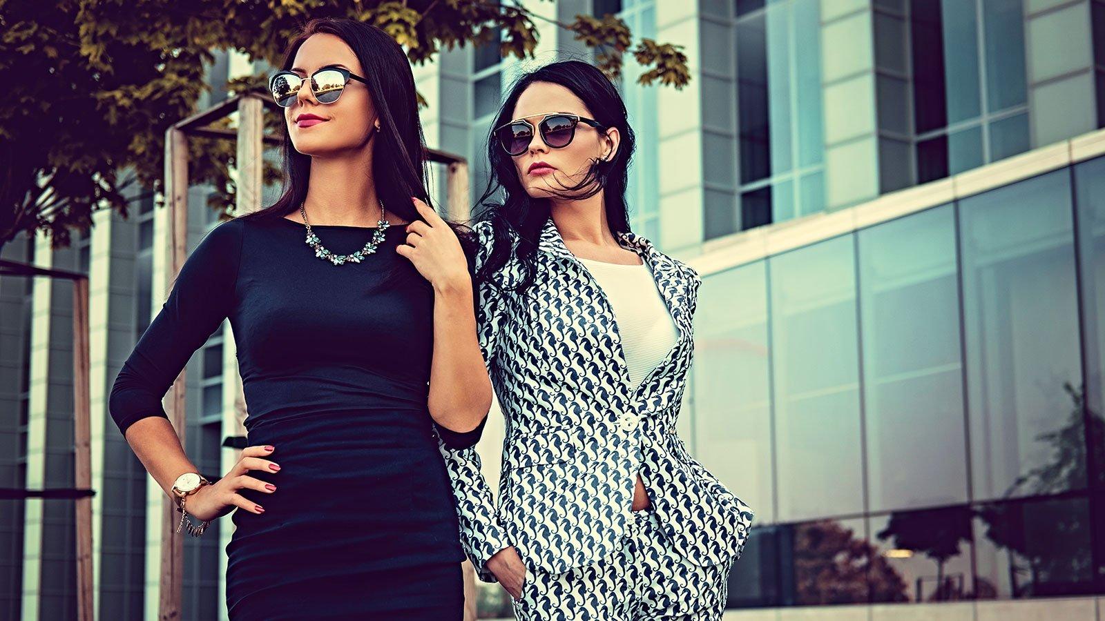 una donna con un vestito di color nero e un'altra donna con un completo di color bianco e nero