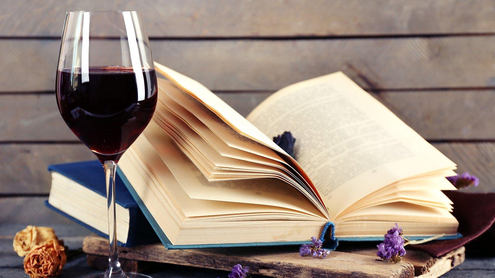 Un calice di vino rosso a fianco a un libro aperto
