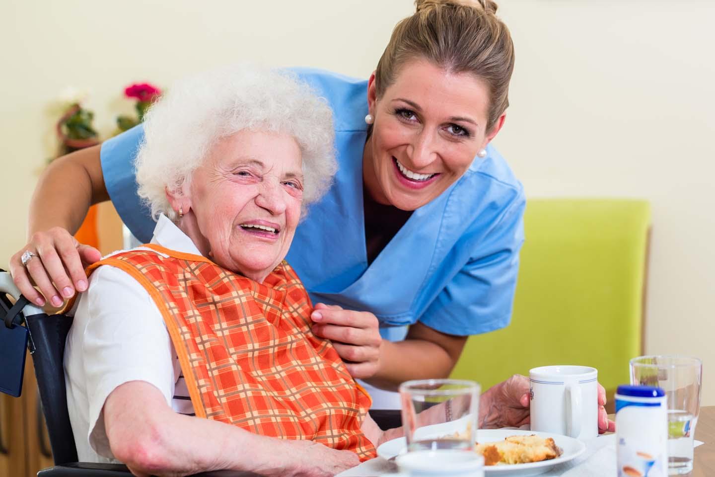 infermiera assiste un'anziana durante il pasto