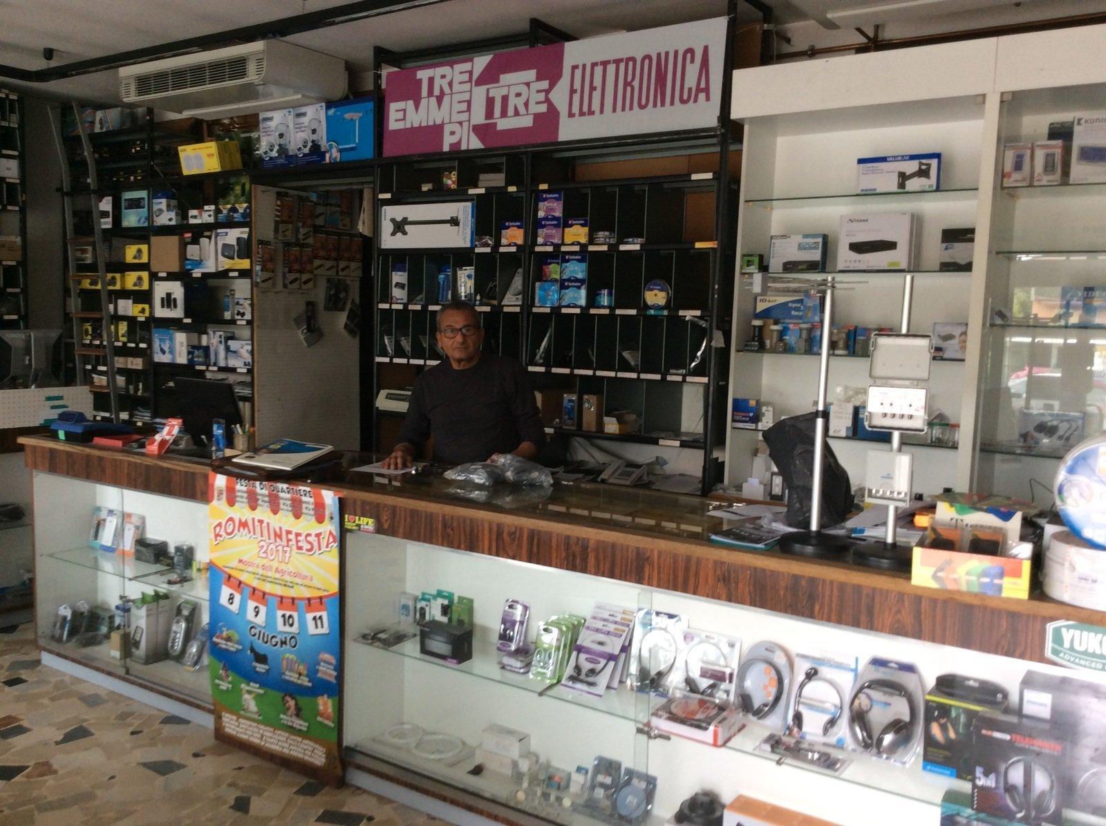 un uomo dietro a un bancone in un negozio di elettronica