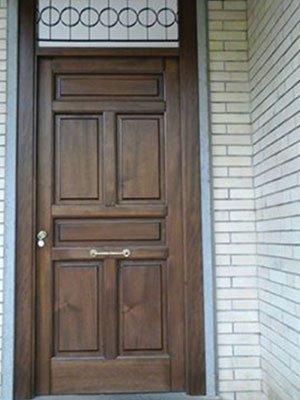 una porta d'ingresso in legno con delle maniglie dorate