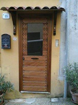 una porta da esterno in legno con un pannello di vetro
