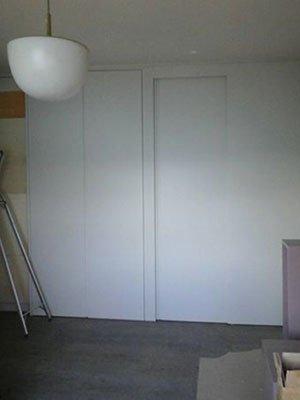 un armadio a muro e accanto una porta di color bianco