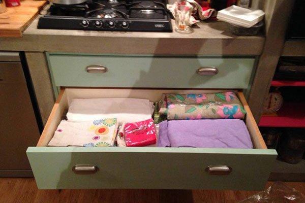 un mobile da cucina con un cassetto aperto con delle tovaglia