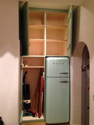 un armadio a muro aperto e accanto un frigo