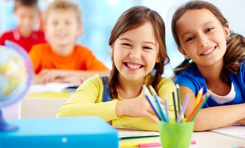 children smiling and studying