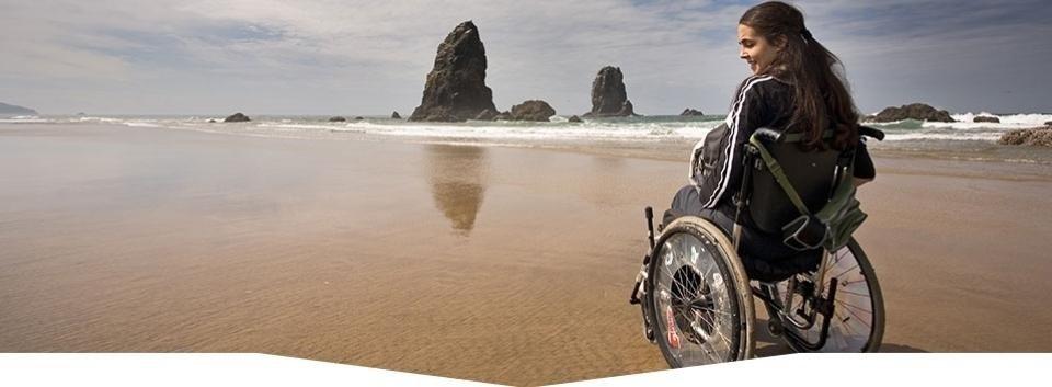 donna disabile nella sedia a rotelle sulla spiaggia