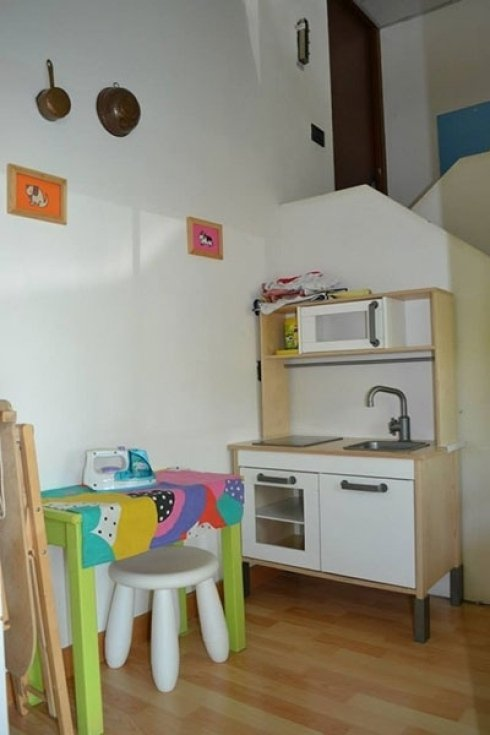 Spazio gioco per bambini con asse da stiro e cucina.