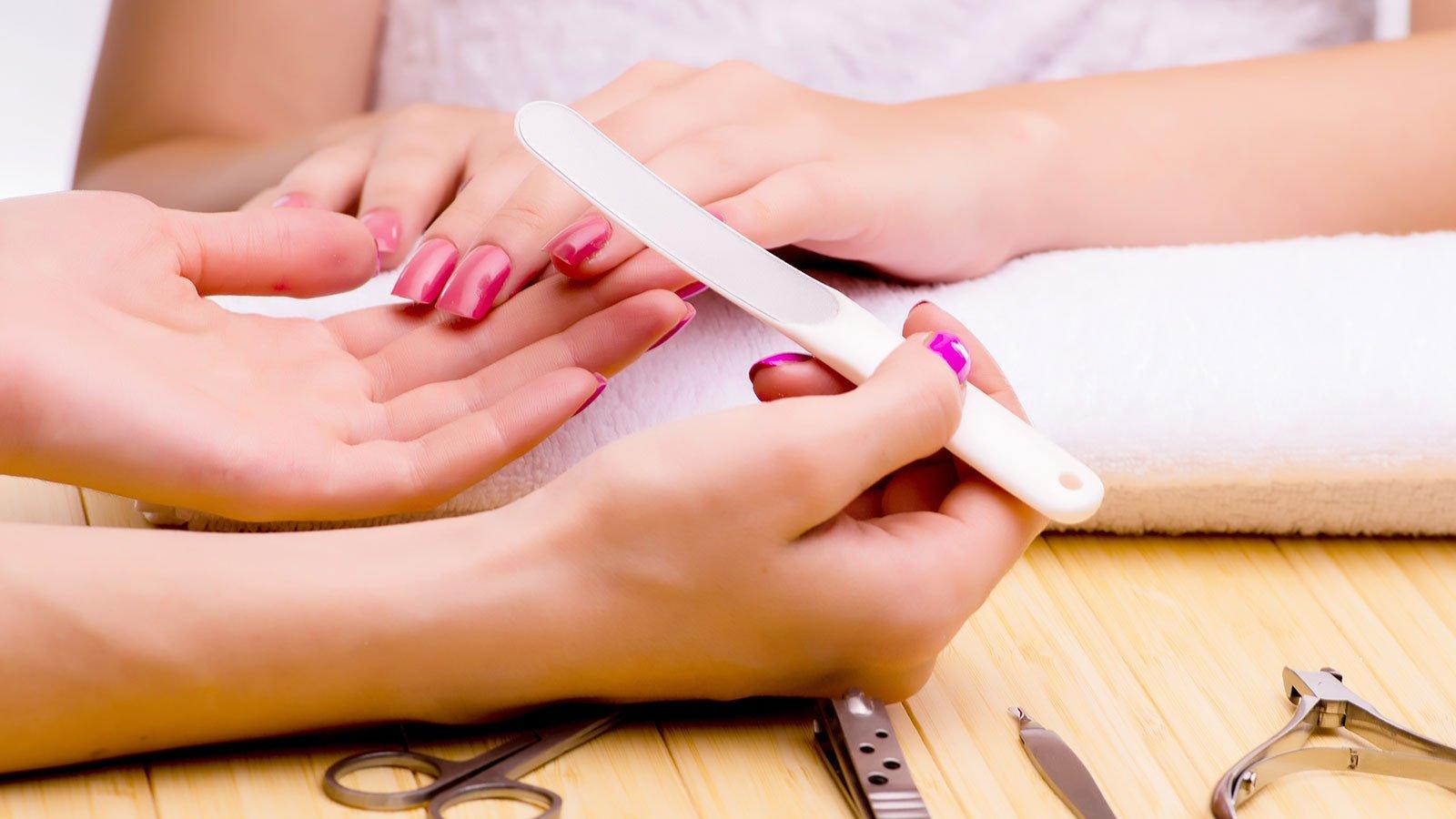 una mano con una lima per le unghie e la mano di un'altra donna con lo smalto fucsia