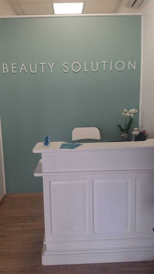un bancone bianco e dietro la scritta Beauty Solution al muro